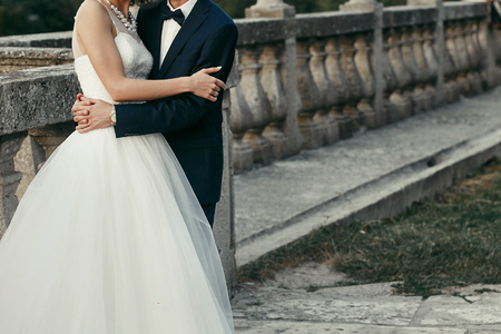 elegant bride and groom gently hugging. wedding couple embracing at old castle in the evening. space for text. man in classic suit with bow tie and woman in white dress with pearls