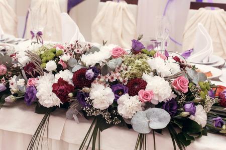 Hermosas flores de ramos rústicos en el centro de mesa de la boda para el novio en el restaurante, recepción nupcial de lujo, decoración elegante Foto de archivo - 77683511