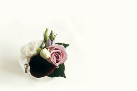 stylish rustic boutonniere on white table with space for text, top view. arrangements for wedding day. getting ready in morning for wedding ceremony
