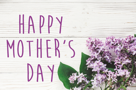 happy mothers day text sign. greeting card. gentle purple lilac flowers on white rustic wooden background. tender soft image. mothers day concept. flat lay