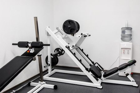 modern gym weight training equipment for exercises and rehab, leg presses. rehabilitation equipment in therapy clinic. fitness wellness concept. space for text Stock Photo
