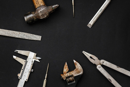 Tools for repairing and renovation concept on black background top view. hammer pliers, screwdriver, calipers, wrench, rasp, chisel. Working tool set and instruments for fixing flat lay, copy space Stock Photo
