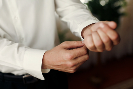 groom getting dressed in the morning, putting on cuff links,wedding preparation