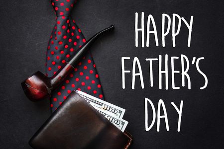 happy fathers day text sign. fathers day greeting card.  flat lay. bow tie leather wallet with money wooden tobacco pipe on black background with space for text, top view.
