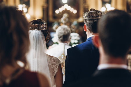golden crowns on couple bride and groom in church during wedding ceremony, religion traditions