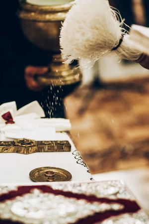 祝福の教会の祭壇の上の金の結婚指輪を結婚式の司祭します。