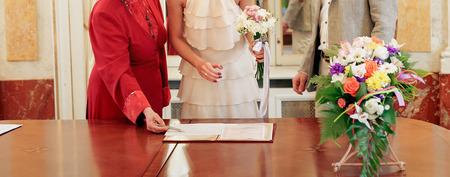 スタイリッシュな高級新郎とヴィンテージの花嫁結婚式宴で署名結婚公式文書登録をドレスアップします。