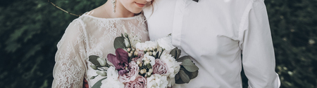 stylish wedding couple with bouquet. modern bride and groom holding fashionable bouquet and embracing in sunny garden. fine art wedding photo, romantic moment
