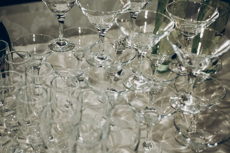 empty glasses of martini in pyramid or tower on table at wedding reception, alcohol bar, catering in restaurant