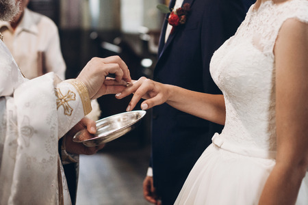 priest putting on golden wedding rings on bride hand in church during wedding ceremony, religion traditions