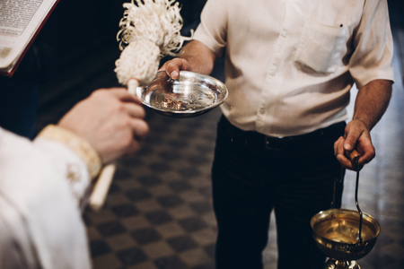 priest blessing golden wedding rings on plate in church before wedding ceremony, religion traditions Stock Photo