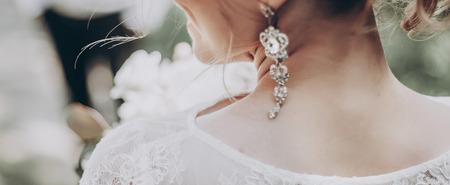 スタイリッシュな結婚式花嫁花束と驚くべきモダンなドレス。日当たりの良い庭でポーズ花嫁イヤリングをクローズ アップ。結婚式の写真、ロマン