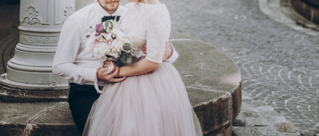 stylish wedding couple with bouquet. modern bride and groom holding fashionable bouquet at old stairs at castle. fine art wedding photo, romantic moment, long edge Stock Photo