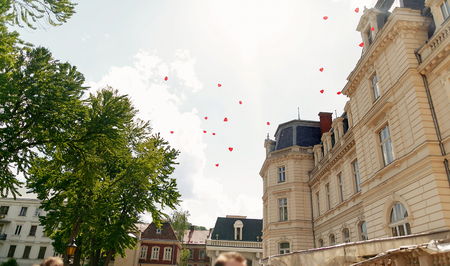 letting: red heart shaped balloons flying up in the sky at wedding ceremony reception in sunny park. guests letting go balloons at outdoor party
