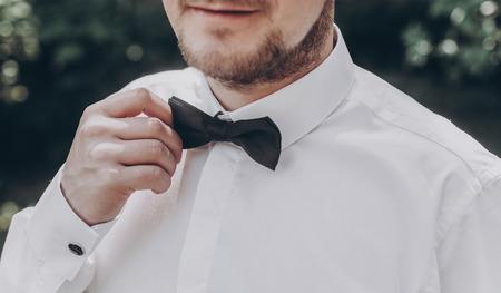 stylish groom in white shirt with black bow tie. wedding groom posing, holding tie,  in sunny garden, fine art wedding photo, romantic moment
