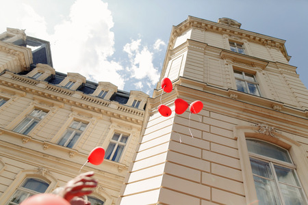 Rode hartvormige ballonnen vliegen in de lucht op bij de receptie van het huwelijksceremonie in zonnig park. Gasten laten ballonnen op buitenfeest