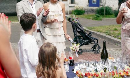 Tostadas en la recepción de la ceremonia de boda. Pareja de boda e invitados con copas de champán. Bar abierto en el parque, familiares y amigos animando con bebidas.