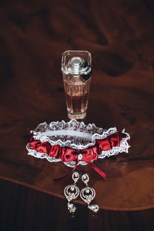 luxe parfumflesje en kouseband op houten tafel, bruid boudoir set. ochtend voorbereiding