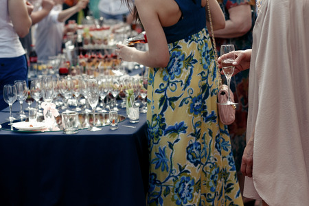 people toasting at wedding ceremony reception. guests holding champagne glasses. open bar in park, family and friends cheering with drinks