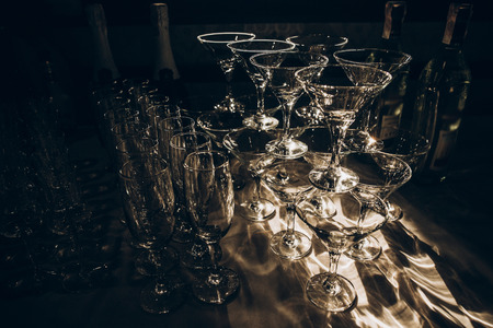 empty glasses of martini and champagne on table at wedding reception, alcohol bar, catering in restaurant
