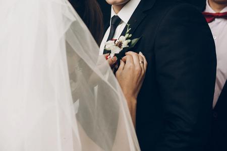 신부 신랑에게 씌우고 빨간색 흰색 꽃의 boutonniere 재킷에 가까이