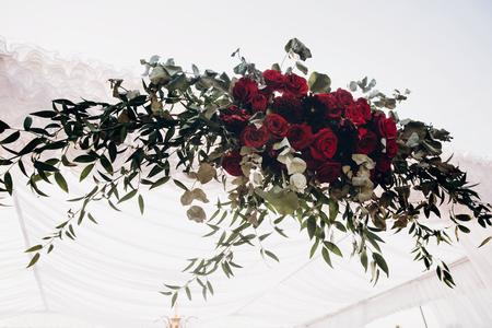 흰색과 빨간색 아치 및 빨간 꽃다발과 공원에서 결혼식 피로연에서 통로