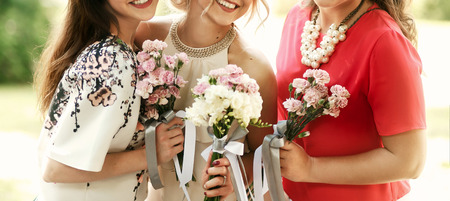 bride in vintage dress and bridesmaids with bouquets smiling and posing in sunny park at wedding reception