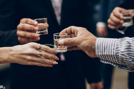 people holding glasses of vodka and toasting at wedding reception, celebration outdoors, catering in restaurant. christmas and new year Stock Photo