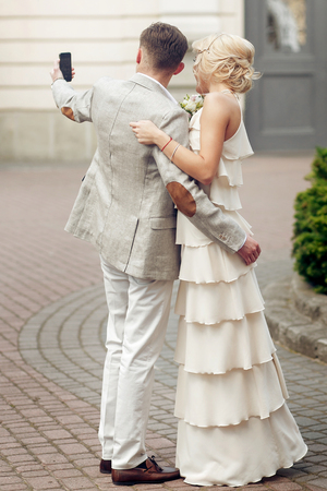 wedding couple making selfie. luxury bride in vintage dress and stylish groom taking photo selfie with phone on background of old building at wedding reception Stock Photo