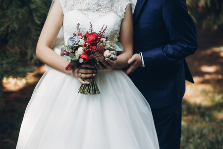 bride and groom holding rustic bouquet of roses and succulents, posing in park. gorgeous wedding couple at reception. boho newlyweds