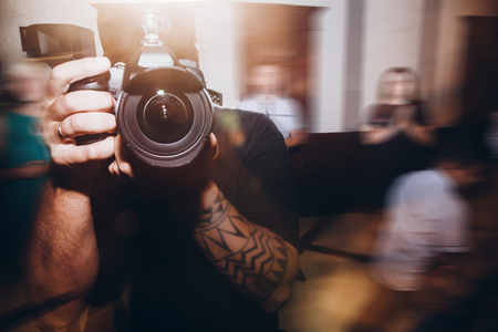 man holding photo camera, photographer at wedding ceremony reception, Stock Photo