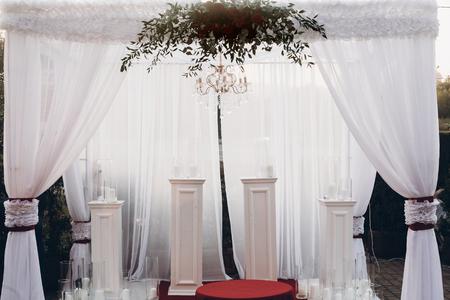 白と赤のアーチと赤い花束を持つ公園での結婚披露宴で通路