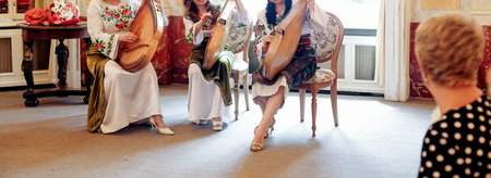 woman playing bandura pandora in ukrainian national embroidery dresses at wedding ceremony reception