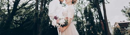 スタイリッシュな結婚式の花嫁と花婿の日当たりの良い公園でハグ官能的な瞬間。光の庭を受け入れる現代のカップル。結婚式の写真、ロマンチッ 写真素材