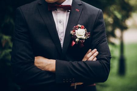 Primo piano dello sposo o dello sposo, papillon e boutonniere sul vestito, uomo alla moda sicuro Archivio Fotografico - 80889220