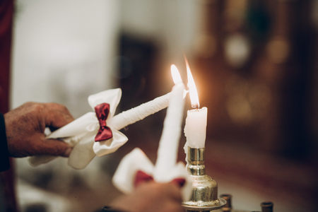 candle lighting up for bride and groom in church during wedding ceremony Фото со стока