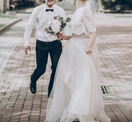 stylish wedding bride and groom having fun in sunny park, happy moment. modern couple running and smiling. fine art wedding photo, romantic tender moment