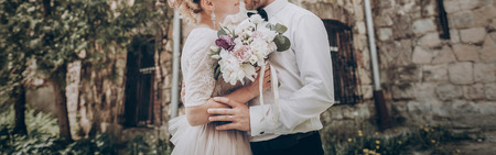 stylish wedding couple with bouquet. modern bride and groom holding fashionable bouquet at old  castle. fine art wedding photo, romantic moment, long edge