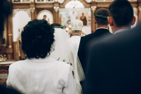 back view of bride and groom and guests priest in church during wedding ceremony Stock Photo