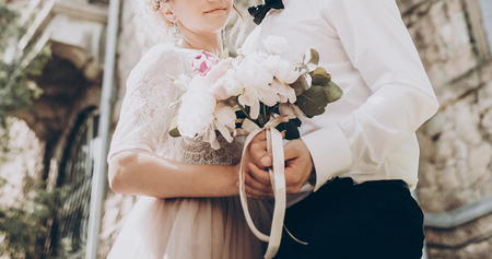 stylish wedding bouquet. modern bride and groom holding fashionable bouquet close up in park. fine art wedding photo, romantic moment