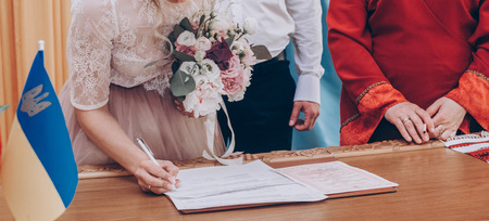 stylish wedding bride and groom signing wedding register. modern couple signs official document in office. romantic tender moment, official wedding ceremony