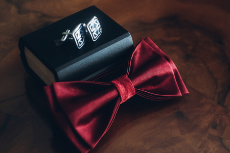 stylish red bow tie and cuff links on wooden table, groom getting ready in morning before wedding. gentleman set