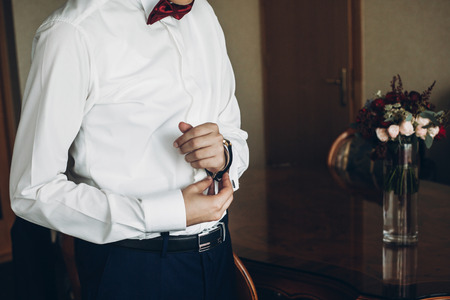groom getting ready in the morning before wedding ceremony, putting on cuff links on shirt