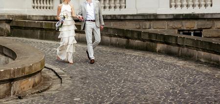 luxe bruid in vintage jurk met boeket en stijlvolle bruidegom wandelen en lachend op de achtergrond van het oude gebouw. gelukkig huwelijkspaar, sensueel romantisch ogenblik, lange rand