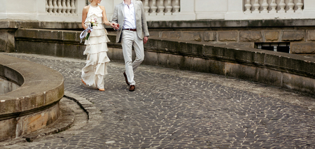luxury bride in vintage dress  with bouquet and stylish groom walking and smiling on background of old building. happy wedding couple, sensual romantic moment, long edge