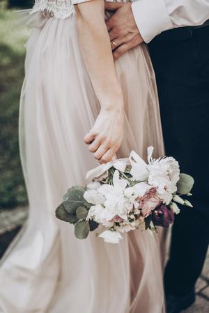 スタイリッシュなウェディング ブーケ。近代的なおしゃれな花束を持って新郎新婦は、公園のクローズ アップ。美術ウェディング写真、ロマンチッ