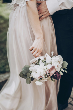 moment: stylish wedding bouquet. modern bride and groom holding fashionable bouquet close up in park. fine art wedding photo, romantic moment