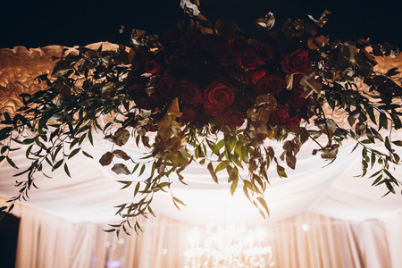 white and red arch and aisle at wedding reception in park, with red bouquet et evening ceremony in light