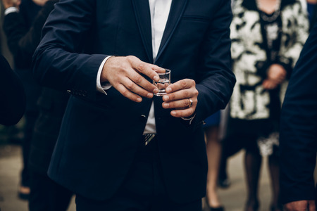 people toasting holding glasses of vodka cheering at wedding reception, celebration outdoors, catering in restaurant. christmas and new year Stock Photo