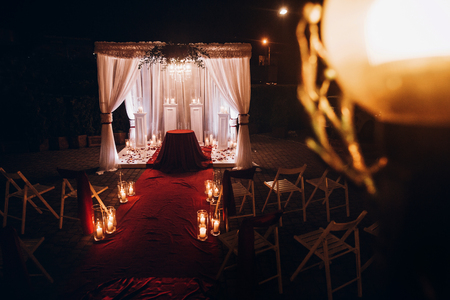 wedding evening decor for ceremony, venue aisle with candles in glass lanterns and arch, stylish wedding decoration for night ceremony in garden, lights. beautiful romantic place